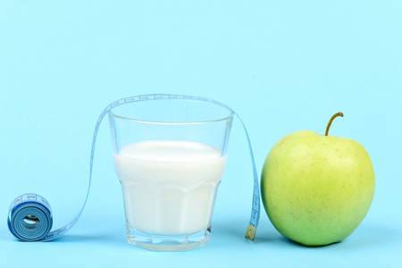 Concept of diet food, vitamins and healthy nutrition: roll of measuring tape near glass of milk and green apple, isolated on light blue background with copy space Stock Photo