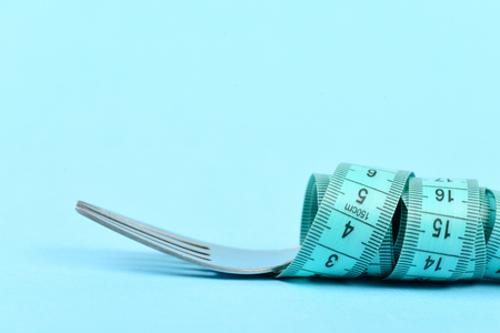 Fork and measuring tape tied around it, isolated on turquoise background with copy space, close up. Concept of health and diet