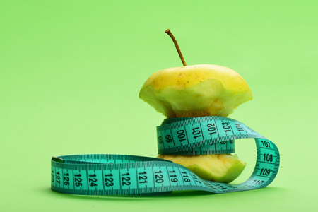 Tape for measuring in greenish blue color wraps around bitten apple on light green background with copy space
