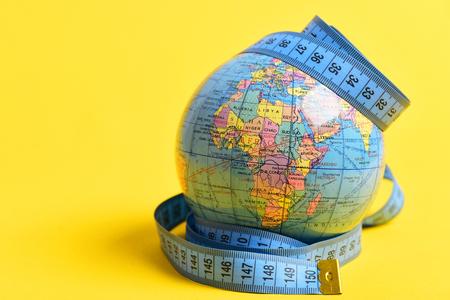世界に孤立した黄色の背景の周りのテープを測定。留学、旅行、グローバリゼーション、遠い旅行の象徴 写真素材