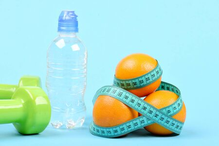 Water in plastic bottle near two green dumbbells and pile of oranges tied around with measuring tape, isolated on light blue background. Concept of fitness and diet Stock Photo