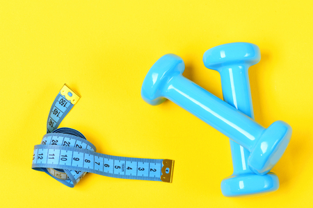 dumbbells or barbell and measuring tape on yellow background, exercise concept Stock Photo