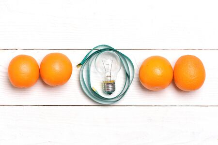Orange fruit line and cyan measuring tape circle with light bulb on light wooden background, top view and copy space. Healthy food idea and fitness concept