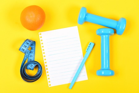 Concept of healthy nutrition and sports with orange fruit, blank page with copy space, blue pen and dumbbells with measure type isolated on warm yellow background, top view