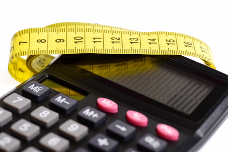 Calculator with 100 number and yellow tape for measuring lying on it, isolated on white background. Concept of calculation calories