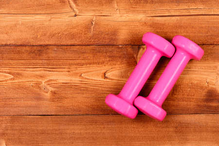 fitness pink dumbbells on brown vintage wooden background, copy space
