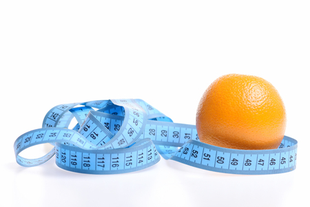 metering: Orange fruit and blue measuring tape wrapped around it isolated on white background, copy space. Concept of healthy food and shape