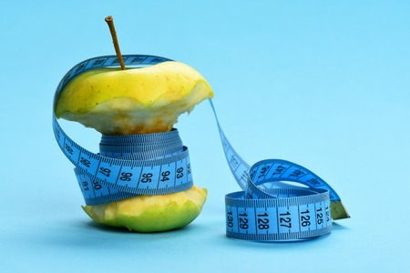 Green apple wrapped tightly with soft measuring tape on light blue background with free end rolled on the side. Diet and fitness concept
