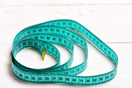 Circles made of cyan measuring tape on white wooden background, selective focus. Concept of measurement and keeping fit Stock Photo