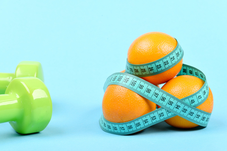 Oranges tied around with turquoise tape for measuring next to plastic dumbbells, isolated on light blue background. Sports concept Stock Photo