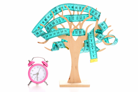 Clock in pink color and decorative wooden tree with cyan tape for measuring, isolated in white background Stock Photo