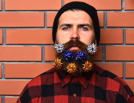 brutal: Bearded man with flowers or bows in long beard. Brutal caucasian serious unshaven hipster in black hat, checkered shirt on brick wall studio background. Party celebration concept