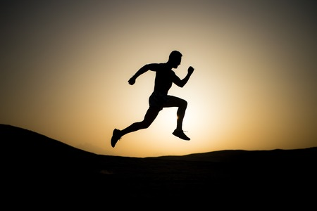 wanderlust: silhouette of running man on sunset fiery sky background in mountain, sport and recreation, future and success, people and nature, speed and healthy lifestyle