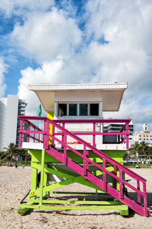 wanderlust: lifeguard tower, wooden colorful station, on sand, sandy beach, tropical palm resort, on sunny day on city skyline with white clouds on blue sky. Idyllic summer vacation. Safety. Observation Stock Photo