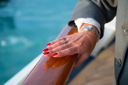 jewerly: Female hands and wrist-watch with red manicure and golden ring on finger with diamonds near water Stock Photo