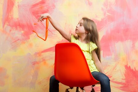kid or baby girl in summer t shirt and glasses on chair on colorful abstract background, home design and fashion Stock Photo