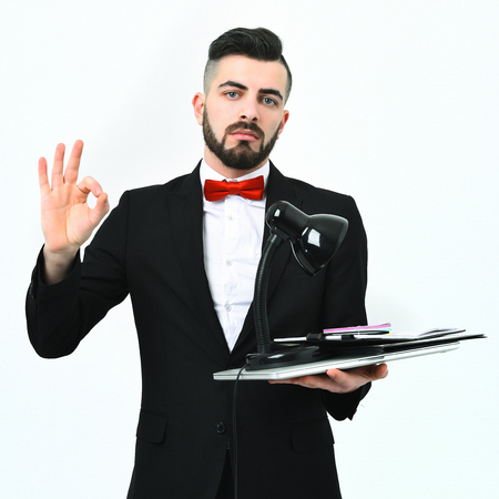 alright: Insurance agent showing OK sign holds office desk appliances and wears official suit and red bow, isolated on white background. Concept of perfect management and success