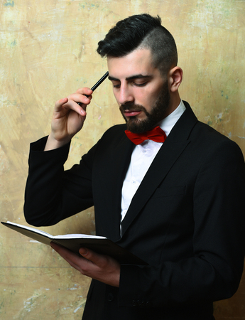 Executive generates ideas. Head manager with beard and classic suit with red bow reads his day list in organizer, old vintage wall background. Business schedule concept Banco de Imagens