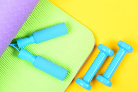 Concept of sports as lifestyle with lightweight dumbbells and blue skipping rope on green and violet yoga mat isolated on yellow background, top view. Sport in trend Reklamní fotografie