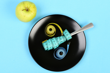 Concept of healthy food and low calorie diet: green apple near black ceramic plate with fork and measuring tapes on it, isolated on light blue background, top view