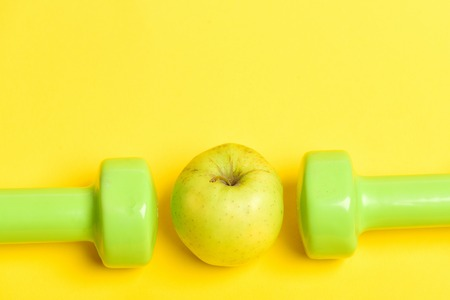 Dumbbells in juicy green colour and ripe greenish yellow apple between them isolated on yellow background, copy space. Concept of healthy nutrition and sportive shape