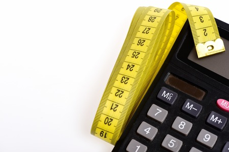 Calculate your diet. Plastic calculator with folded yellow sewing centimeter isolated on white background. Concept of dieting and measurement Stock Photo