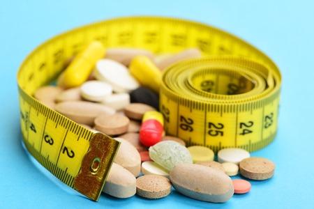 Vielzahl von Pillen und von gelbem Maßband, oben lokalisiert auf hellblauem Hintergrund, Abschluss, selektiver Fokus Standard-Bild