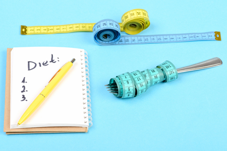 Concept of diet, weight management and planning: notepad with written diet checklist and yellow pen on it, measuring tapes and metal fork, isolated on light blue background