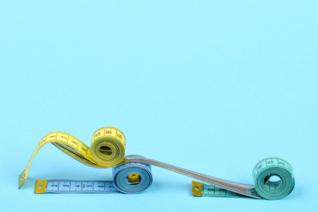 Fork made of metal and measuring tapes in different colors, isolated on turquoise background with copy space. Concept of healthy nutrition for slim shape Stock Photo