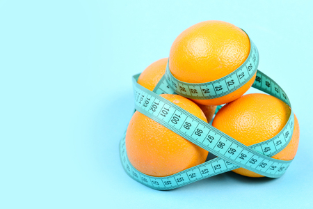Oranges wrapped around with turquoise tape measure, isolated on light blue background with copy space. Symbol of vitamins, fruit diet and health