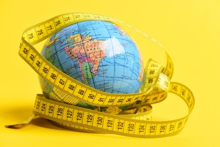 Concept of long distant travel: globe wrapped around with measuring tape isolated on bright yellow background Foto de archivo