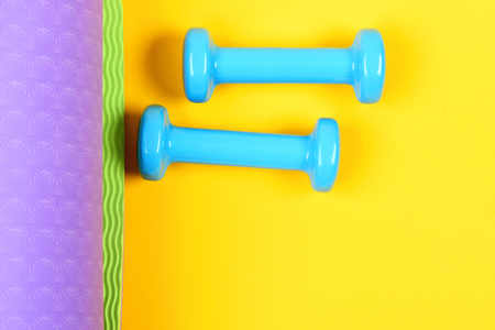 Yoga mat in purple and green colours with blue dumbbells isolated on yellow background, top view and copy space