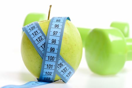 Weight loss concept. Blue measuring tape around fresh apple and green lightweight dumbbells on white background. Health and sports