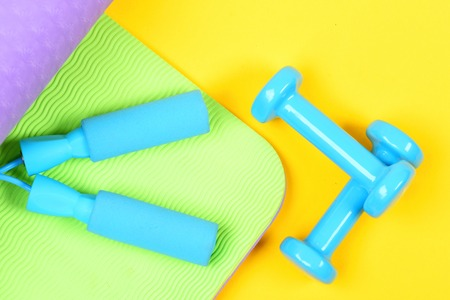 Set of sports equipment holding blue skipping rope handles on green yoga mat and dumbbells crossed against each other isolated on yellow background, top view. Sports and perfect shape concept