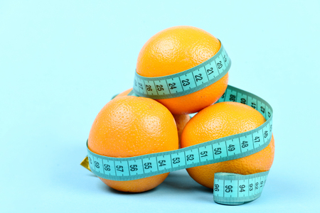 Pile of oranges wrapped around with cyan tape for measuring, isolated on light blue background. Concept of vitamin diet and healthy lifestyle