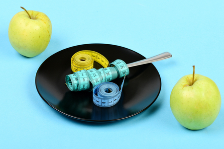 Apples and black ceramic plate with measuring tapes in rolls and wrapped around fork, isolated on light blue background