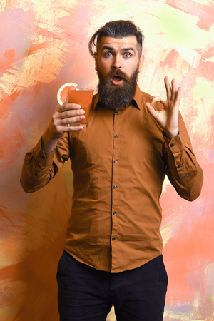 Bearded man, long beard. Brutal caucasian surprised hipster with moustache in brown shirt holding tropical alcoholic fresh cocktail with orange piece on colorful texture background