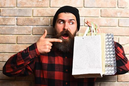 money packs: Bearded man, long beard. Brutal caucasian surprised hipster with moustache holding shopping packages in red black checkered shirt on beige brick wall studio background