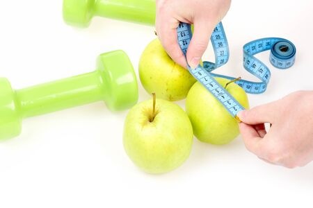 metering: Measures after diet. Female hands hold turquoise measuring tape and metering apple lying among other fruit and green dumbbells, isolated on white background