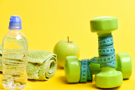 Sports and diet set: bottle with water, towel, apple and green dumbbells wrapped with blue measure tape isolated on yellow background. Concept of health