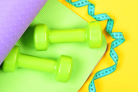 Measuring tape in cyan colour twisting around dumbbells on purple and green yoga mat isolated on yellow background, top view. Fitness and shaping concept Reklamní fotografie