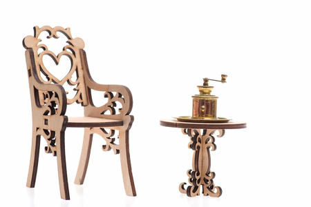 Antique vintage brass coffee grinder on golden tray on decorative wooden table with chair isolated on white background, copy space