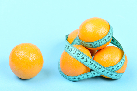 Pile of oranges wrapped around with cyan flexible ruler and another orange fruit put aside, isolated on turquoise background. Vegetarian food concept
