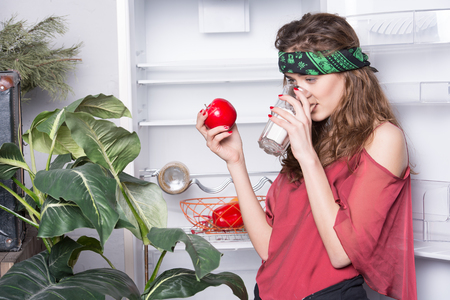 hankie: pretty girl or sexy woman hippie with cute face in green handkerchief or bandana on curly hair near fridge, plant drink from glass and holds red apple