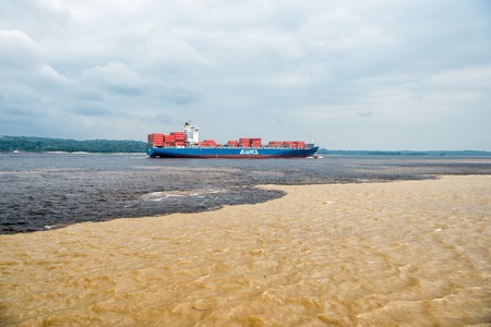 Manaus , Brazil- Decemcer 4, 2015: water meeting in Brazil -amazon river with rio del negro clean and dirty river water with different streams. Cargo ship paasing water meeting Redakční