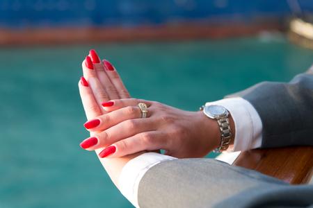 Mani femminili e orologio da polso con il manicure rosso e anello d'oro al dito con diamanti in prossimità di acqua Archivio Fotografico - 80580649