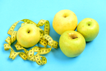 Tape for measuring or flexible ruler and green apples, isolated on light blue background as a symbol of low calorie food Stock Photo