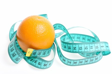 metro de medir: Concept of fresh food eating with ripe orange fruit and cyan blue measuring tape isolated on white background. Diet and health