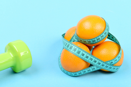 Dumbbell in light green color near pile of oranges with cyan measuring tape, isolated on light blue background. Concept of fitness and dietary