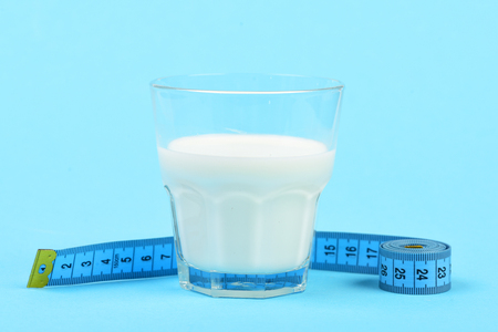 metering: Concept of healthy lifestyle and vitamin nutrition: glass of milk and blue tape measure, isolated on light blue background
